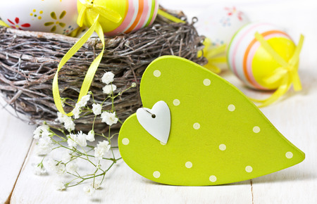 Easter decoration with green wooden heart, nest, decorative eggs, Gypsophila on wooden background photo