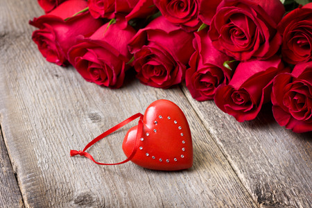 red heart and a bouquet of red roses on a wooden background photo