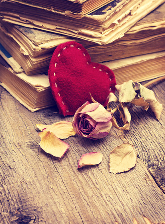 Valentine decorations with heart, dry rose, old book on a wooden  photo