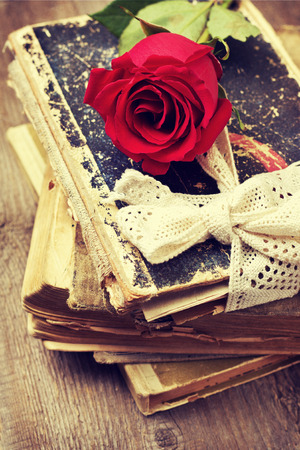 red rose on old books in vintage style photo