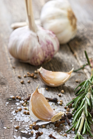 garlic, rosemary, salt, various spices on wooden  photo