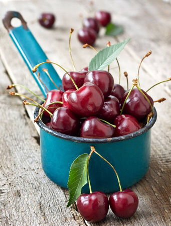 fresh cherries in the old enamel ladle on a wooden background photo