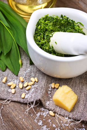 pesto ramson in a white mortar, fresh wild garlic, pine nuts, parmesan and olive oil on a wooden background