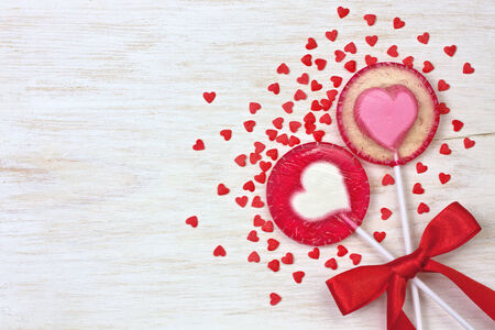 two red heart lollipops on wooden background photo