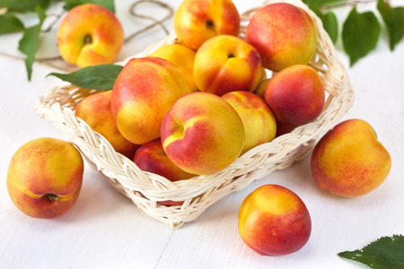 fresh peaches (nectarines) in a basket on a wooden background 스톡 콘텐츠