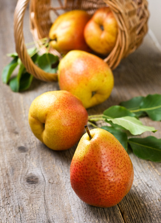 Fresh pears in a basket on a wooden background photo