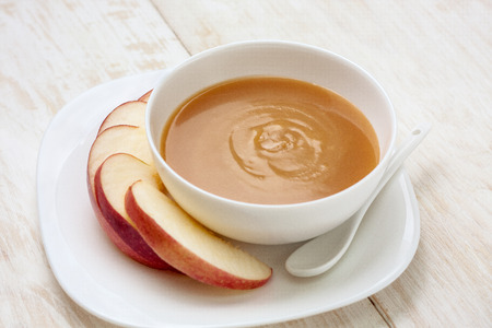 caramel sauce in a bowl and apple slices on a white plate