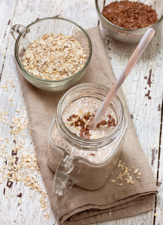 smoothies with  oatmeal,  flax seeds in glass jars on a wooden background 스톡 콘텐츠