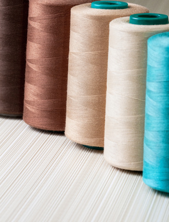 several spools of thread of beige and turquoise color
