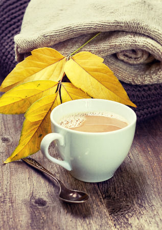 warm things: cup of coffee, warm woolen things autumn leaves on a wooden background (vintage style, toning)
