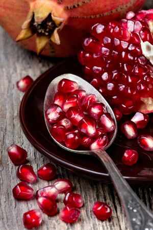 pomegranate: old spoon with pomegranate seeds, slices of pomegranate on a wooden background