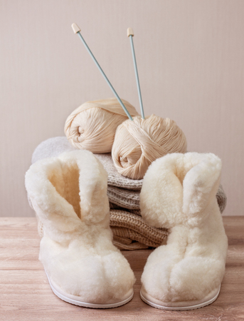 Pair of warm winter sheepskin slippers (alpaca), wool yarn, knitting needle  on a pile of warm woolen clothes (Selective focus)