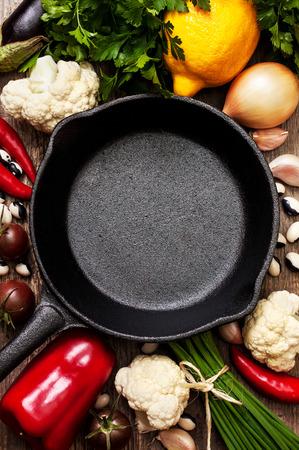 木製の背景に健康的なベジタリアン料理の準備のため鉄鍋と新鮮な野菜をキャストします。 写真素材