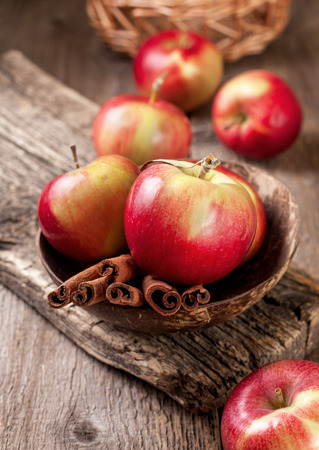stick of cinnamon: cinnamon sticks and apples on the old wooden background Stock Photo