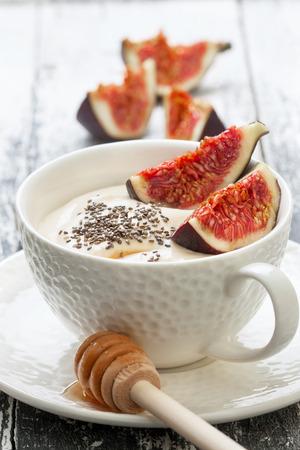 yogurt: yogur con trozos de higo, las semillas de ch�a, la miel en una taza blanca sobre un fondo de madera Foto de archivo