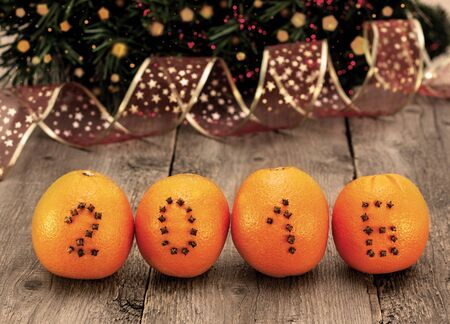 orange: Christmas decorations with oranges and numbers of cloves on a wooden background Stock Photo