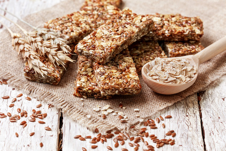 cereal bars, oatmeal, flax seeds on a wooden background