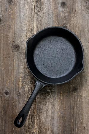 古い木製の背景の空の鋳鉄鍋