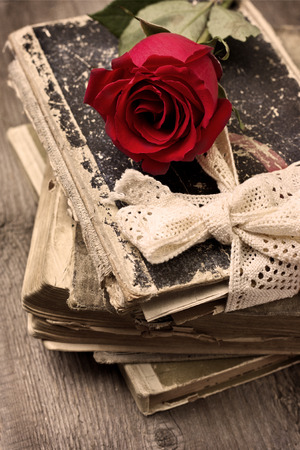 writing desk: red rose on old books on the old wooden background  in vintage style Stock Photo