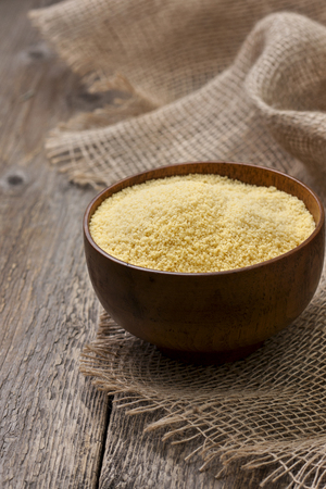 couscous: Couscous in a wooden bowl on a wooden background