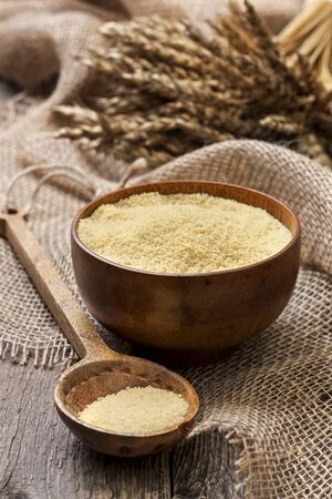 couscous: Couscous in a wooden bowl on a wooden background and sacking