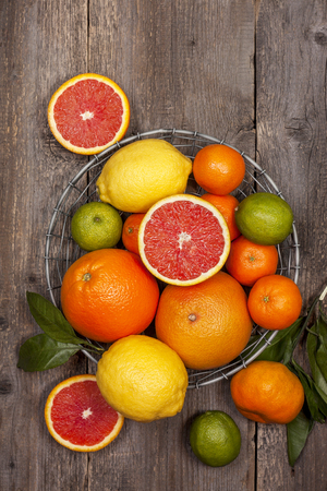 Different fresh citrus fruit in a basket on old wooden background (Top view ) Standard-Bild