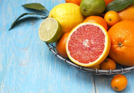 青い木製の背景にバスケットの異なる新鮮な柑橘系の果物 写真素材