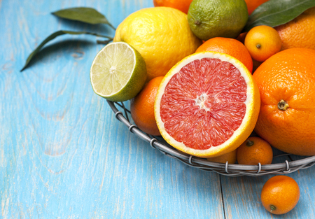 Different fresh citrus fruit in a basket on a blue wooden background