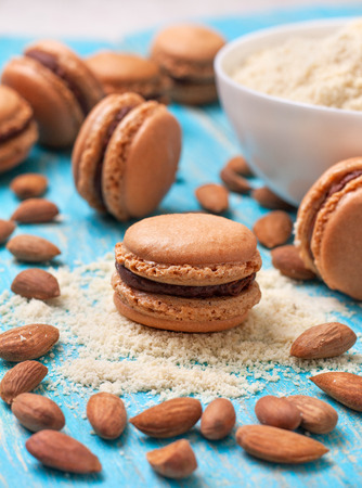 ganache: macaroon with chocolate ganache and almond flour , almonds on a wooden background