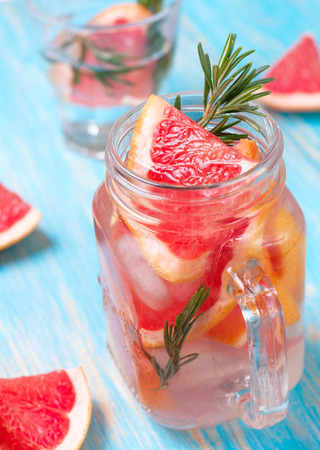 lemonade with grapefruit and rosemary in a mason jar on a blue background