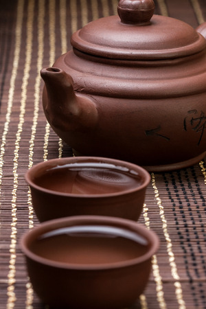 for tea: ceramic teapot and two cups for the tea ceremony on the bamboo napkin (dark) Stock Photo
