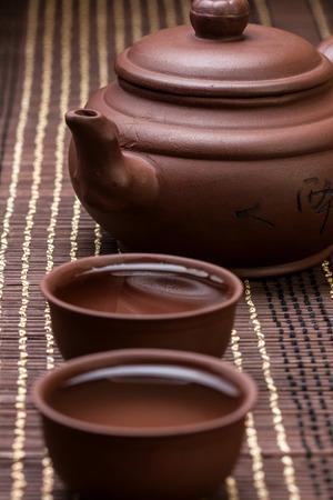 feier: Keramik-Teekanne und zwei Tassen für die Teezeremonie auf dem Bambus-Serviette (dunkel)