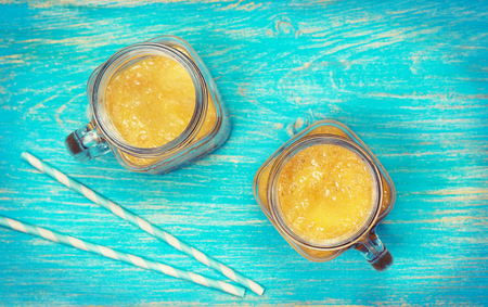 yellow fruit smoothies in mason jars on a blue wooden background (top view, toning) Standard-Bild