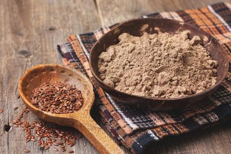 木製の背景 (グルテン フリー ダイエット) のボウルに、亜麻の種子の小麦粉、亜麻