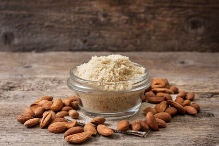 almond flour in a wooden bowl, almonds on old wooden background Stockfoto