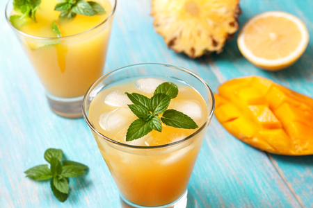 mango ice tea with mint in a glass on blue wooden background