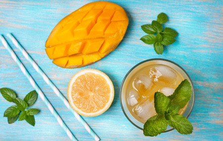 mango ice tea with mint in a glass  on  blue  wooden background (Top view )