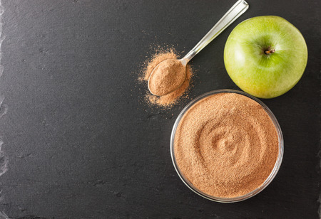 crushed apple fiber, apple green on a black background with space for text (top view). dietary product Stock Photo