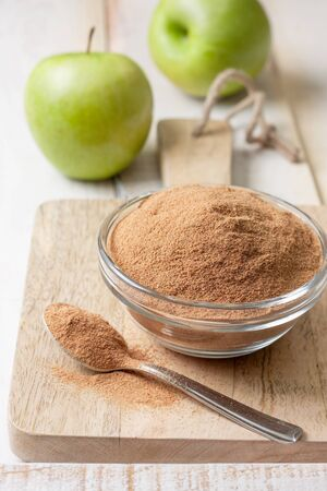 crushed apple fiber, green apples on a light wooden background. dietary product