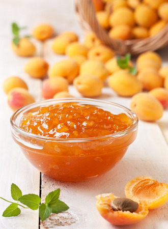 Apricot jam in a glass bowl, fresh apricots in a basket on a light wooden background