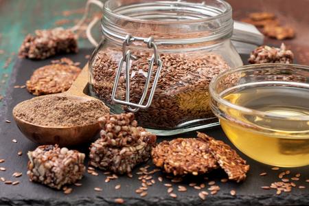 亜麻の種子とその生産物: 亜麻仁油、小麦粉、亜麻、エネルギーバー、亜麻からクラッカー種子暗闇の中に石の背景