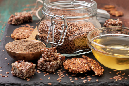 linseed: flax seeds and products thereof: linseed oil, flax flour, energy bars and crackers from flax seeds on a dark a stony background