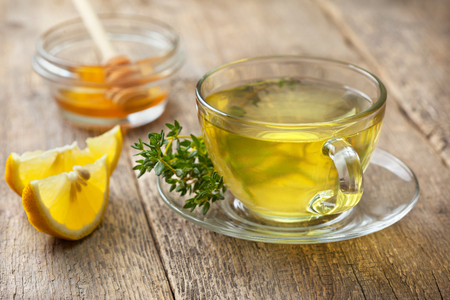 thyme tea in glass cup, sprig of fresh thyme, lemon slices, honey on the old wooden background