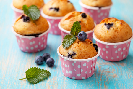 blueberry muffin: blueberry muffins in pink cases, fresh mint on blue wooden background