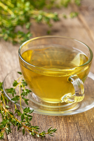 water thyme: cup of thyme tea, fresh thyme on the old wooden background