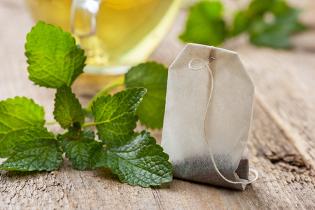tea bag with mint, mint tea cup on the old wooden background