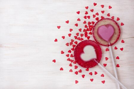 two lollipop-heart on a plate on wooden background (top view)