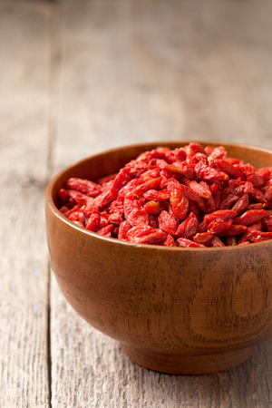 barbarum: Goji berries in a wooden bowl on the old wooden background