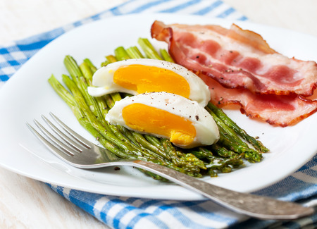 healthy breakfast:  boiled egg, baked asparagus on a wooden background close up