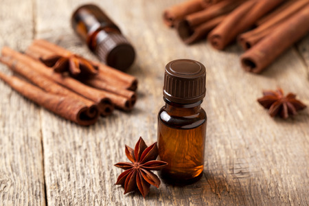 essential oil in a glass bottle with cinnamon, anise on old wooden background